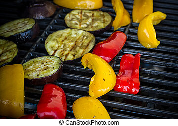 Red and yellow peppers, eggplant slices on grill rack