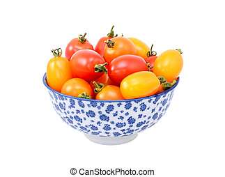 Red and yellow plum tomatoes in a blue and white china bowl