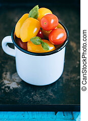 Red and yellow small cherry tomatoes, and green basil in an enamel mug on a black tray