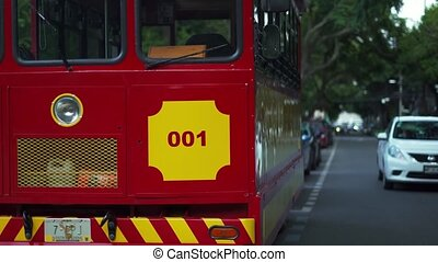 4k Up-close video of a red and yellow trolley car parked on the street and surrounded by trees and cars