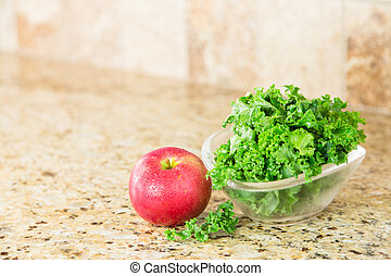 Red apple and a bowl of fresh green kale on a granite countertop