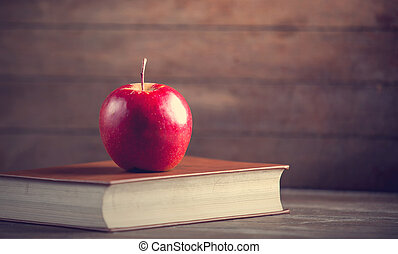 Red apple and book on a table.