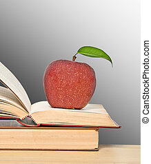 Red apple and books on desk