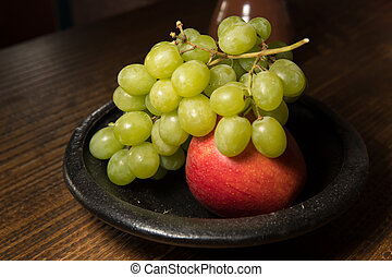 Red apple and green grapes on a black plate