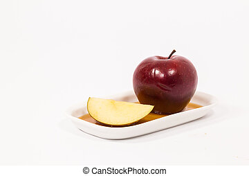 Red apple and red apple slice on white plate with honey...
