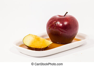 Red apple and red apple slice with drops of honey on white...