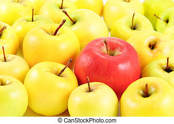 red apple between yellow apples as different concept