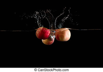 red apple falls into water