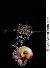 red apple fell into the water on black background