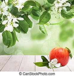 Red apple fruits on white wooden table against abstract green leaves background