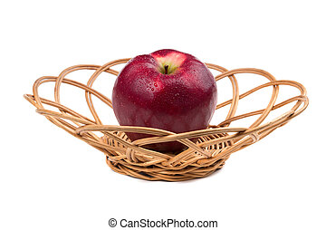Red apple in wicker. Isolated on white