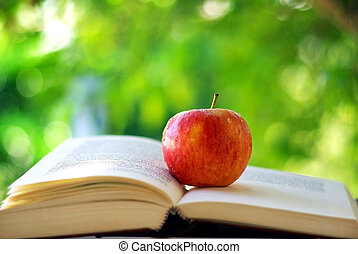 Red apple on a book.