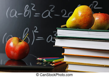 red apple on notebook with book stack