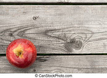 Red apple on old wooden table from above
