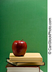 red apple on school books with green background