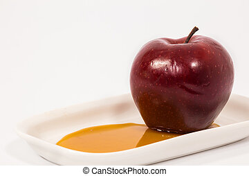Red apple on white plate with honey isolated on a white...