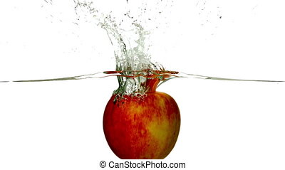 Red apple plunging into water on white background in slow...