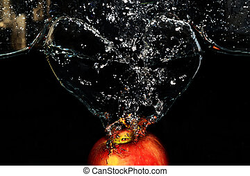 Red apple splashes in the water on black background