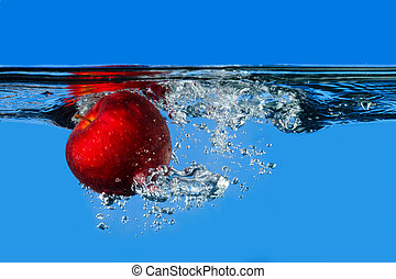 Red apple splashing in water with blue background
