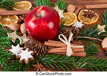 Red apple with christmas spices and fir branch on wooden background