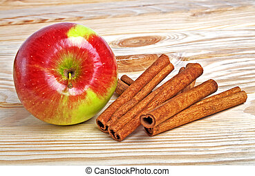 Red apple with cinnamon on wooden background