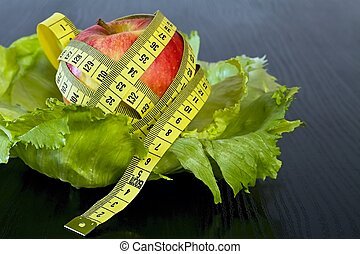 Red apple with measuring tape on a sheets of ice salad.