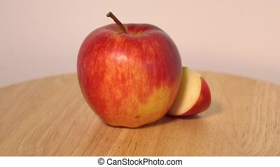 Red apple with slice rotating on wooden table