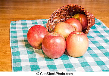 Red apples and cornucopia on checked cloth
