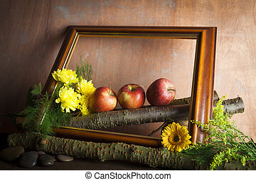 Red apples and flowers in wooden frame
