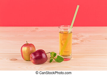 Red apples and glass of juice.