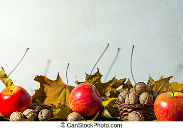 red apples and nuts on a autumn background