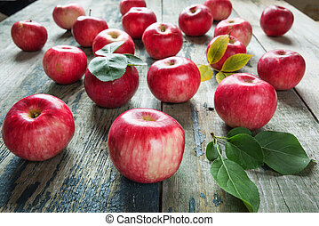 Red apples are on the old wooden table
