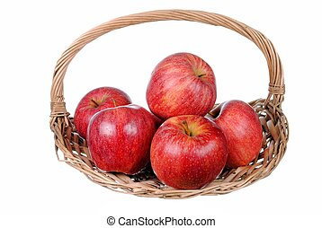 red apples in a straw basket, isolated on white