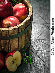 Red apples in a wooden bucket.