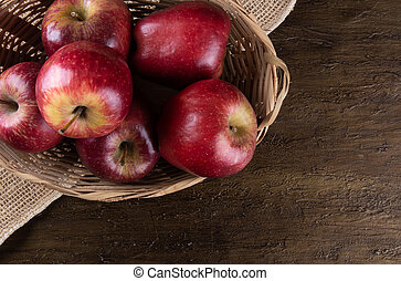 Red apples in basket with wooden background. Top view.