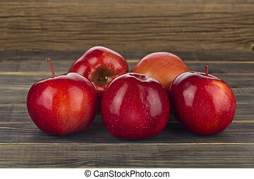 Red apples on a wooden background close-up.
