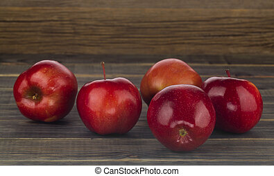 Red apples on a wooden background.