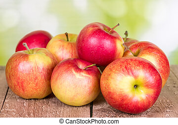 Red apples on an old wooden surface.