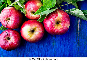 Red apples on blue wooden background. Top view. Copy space.