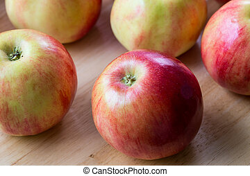 Red apples on brown wooden background, natural food.