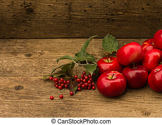 red apples with leaves on wooden background
