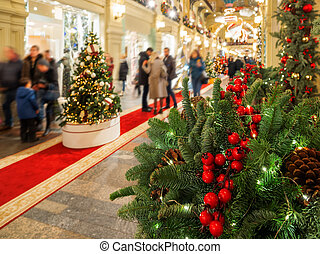 Red artificial berries for Christmas tree in mall. Traditional decoration for New Year celebration. Interior of store with people on background.