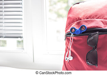 red backpack with school supplies on light background