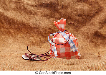 red bag and buttons with rope on a background of burlap