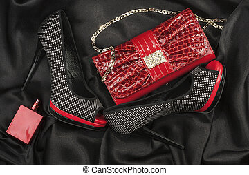 Red bag, shoes and perfume lying on black satin