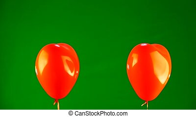 red ball in the form of heart on a green background