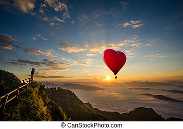 Red balloon in the shape of a heart, Colorful hot-air balloon flying over the mountain