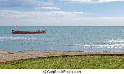 Red barge in the sea. Ostia, Italy