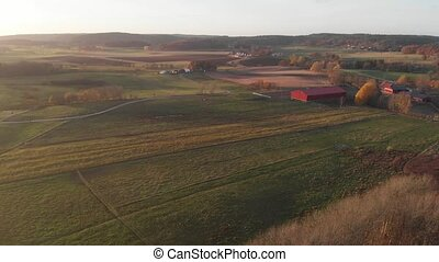 Red Barn and Farm Field at Sunset, Aerial Forward. High quality 4k footage