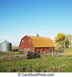 Red barn and fence in field.